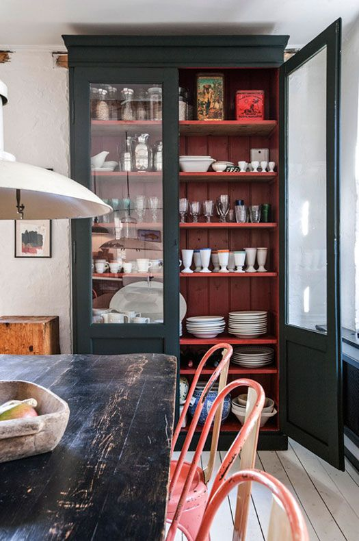 Farmhouse kitchen with a black cabinet made out of antique French doors with a painted red interior.