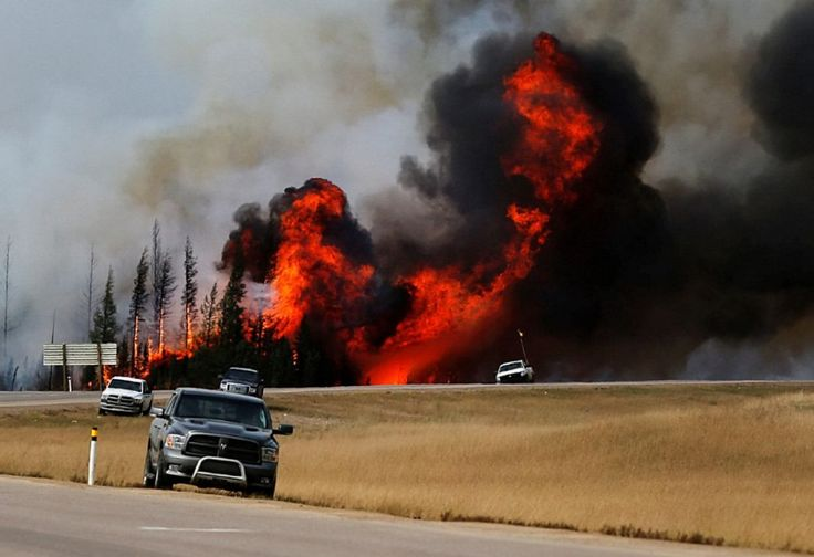 Smoke and flames from the wildfires erupt behind cars on the highway near Fort McMurray, Alberta...May, 2016