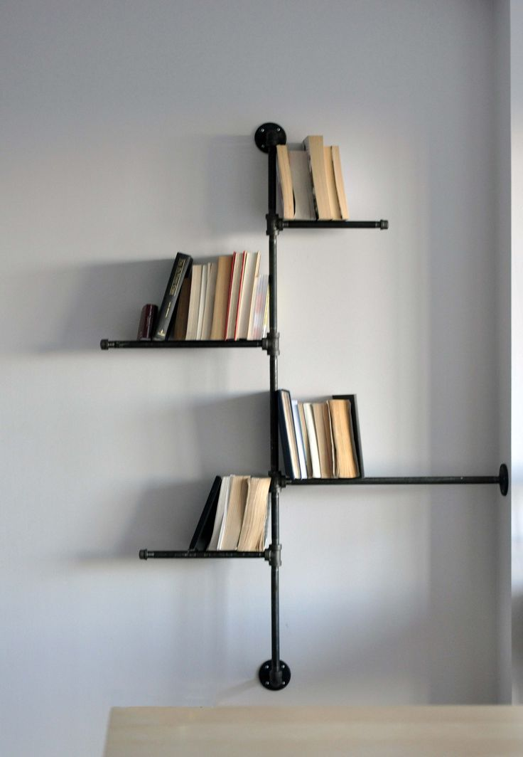 "Simple, attractive lines in this metal bookshelf. Think the ""shelves"" are just metal rods though - I may prefer perspex/wood support to avoid books falling through the gap."