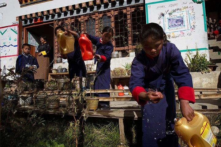 L'importanza di coltivare (sé e quel che ci circonda).  (L'approccio all'educazione in Bhutan spinge ad insegnare ai come rispettare la natura che ci circonda e ad avere come orizzonte la sostenibilità. La scuola elementare Jigme Losel a Thimphu, è considerata un modello: ogni classe ha i suoi alberi di cui si deve curare e ci sono orti e giardini di cui si occupano direttamente gli studenti e le studentesse).  Ph: Jean-Baptiste Lopez