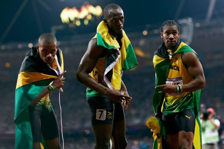 London 2012 - Jamaican athletes sweep the men's 200m sprint and celebrate wearing flags of their nation. Warren Weir (L) took the bronze, Usain Bolt (center) won gold, and Yohan Blake (R) earned the silver.  IOC/John Huet