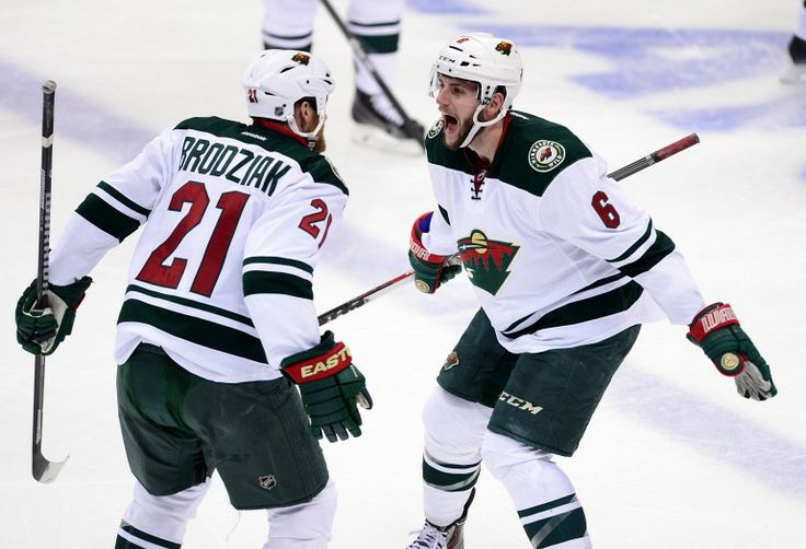Apr 30, 2014; Denver, CO, USA; Minnesota Wild defenseman Marco Scandella (6) and center Kyle Brodziak (21) react to the win over the Colorado Avalanche in a overtime period in game seven of the first round of the 2014 Stanley Cup Playoffs at Pepsi Center. Mandatory Credit: Ron Chenoy-USA TODAY Sports