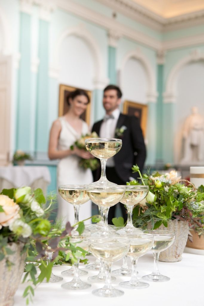 Bride and groom at Royal College of Physicians Dublin with wedding cake, champagne bowls and floral decoration