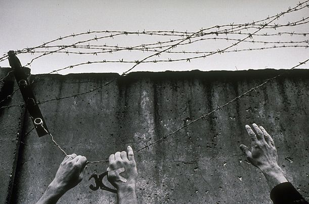 Freedom East and West German hands join in tearing down barbed wire from top of the wall on December 1, 1989.