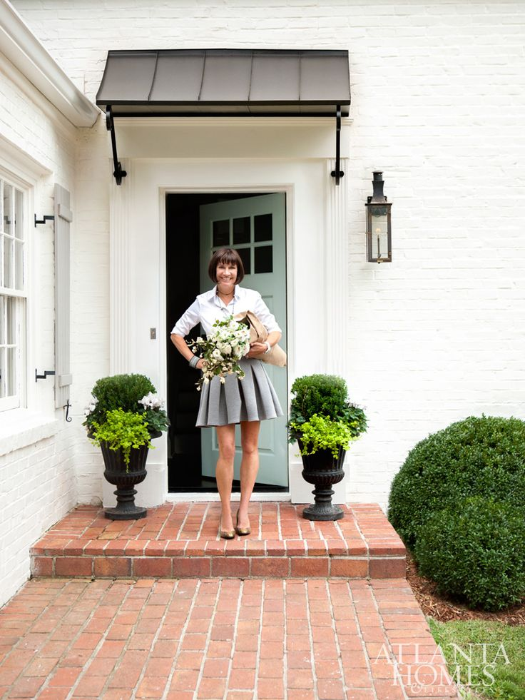 Meg Harrington in front of her front door, painted Wythe Blue by Benjamin Moore.