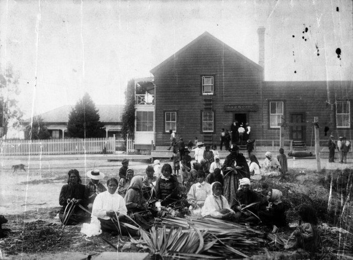 The Geyser Hotel, Whakarwarewa with a group of women in the foreground, 1880s Reference Number: 1/2-008570-F Shows the Geysor Hotel, Whakarewarewa, in the 1880s with a group of Maori women in the foreground weaving flax. Shows the original hotel, a portion of which is incorporated in the second hotel.