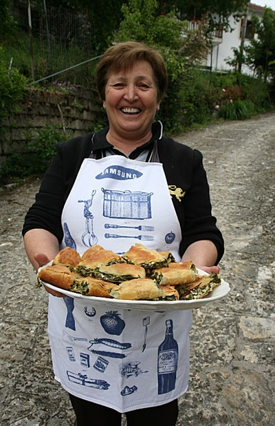 Scenes from Epirus, Greece: A home cook with a plate of fresh-baked wild greens pie in the village of Zitsa, in Epirus.