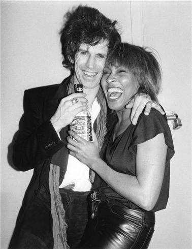 Tina Turner & Keith Richards in a Jack Daniels moment. By Bob Gruen.