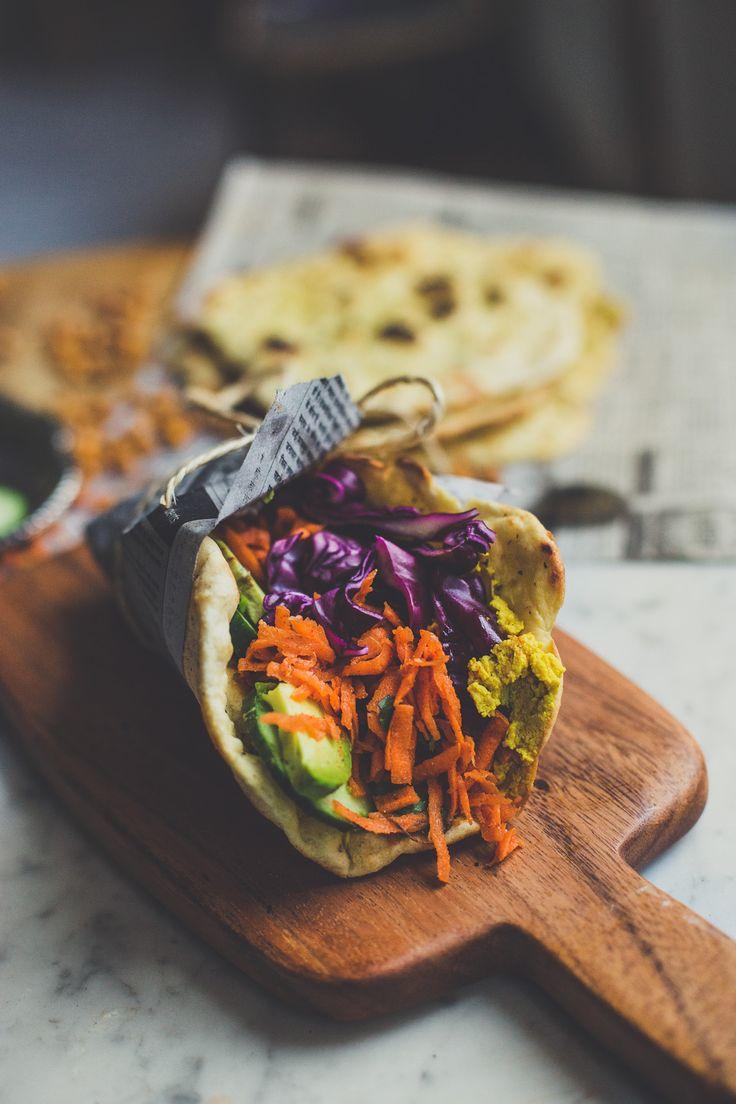 Homemade vegan naan met kerriehummus, geroosterde kikkererwten, wortelsalade en andere veggies.