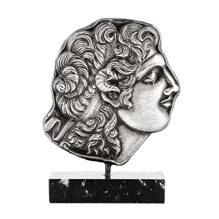 Relief plaque of the head of Alexander the Great, that is inspired by a gold medal of Tarsus. The plaque is mounted on a marble base. 3rd century B.C., Ciliicia  Dimensions: 10cm x 15,5cm x 3cm Bronze, plated in silver solution 999°