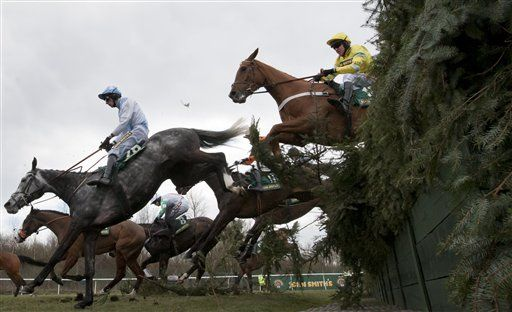 Triolo Dalene ridden by Barry Geraghty, right, clears Beechers Brook on his way to winning the Steeple Chase during Ladies Day at Aintree Racecourse Liverpool, England, Friday, April 5, 2013. (AP Photo/Jon Super)