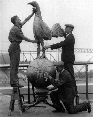 "A famous poster of a statue being cleaned at Tottenham  Hotspur grounds.  There is no suggestion of anything here other than hygenic diligence.  The poster is titled ""The Cleaning of the Cockerel""."