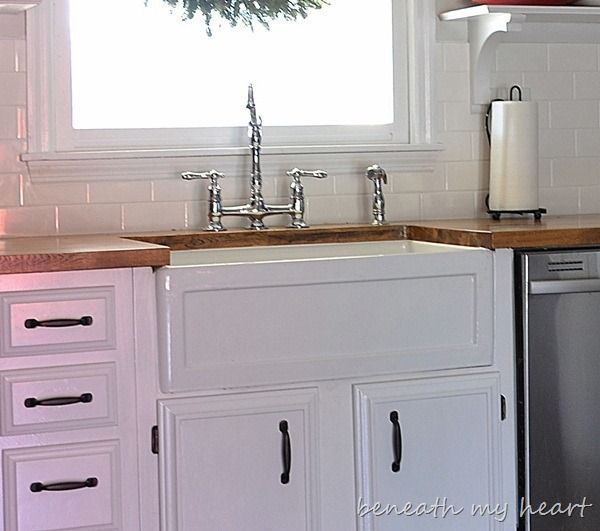 love the big white farmhouse sink with the white cabinets and butcher block countertops