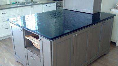 Un comptoir d'îlot de cuisine fait de verre thermoformé bleu et réalisé par Verre Design/ A kitchen island done with thermoforming glass
