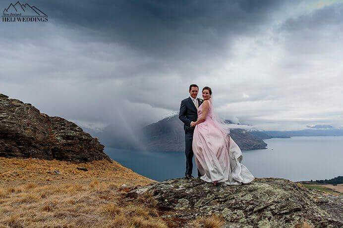 Wedding on mountain top in Queenstown with stormy weather.  coming in Bride & Groom