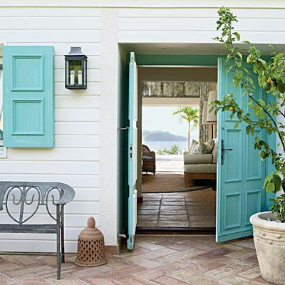 Tropical Tone: Add Caribbean character to your outdoor entry with a few fresh coats of turquoise paint for a statement entry. This tropical hue combined with island accents such as a curvaceous metal porch bench makes for a welcoming invitation to paradise.
