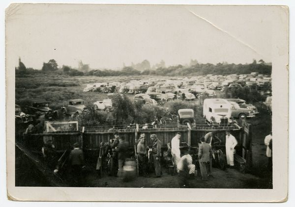 """Motorbikes at the Aranui Speedway, off Rowan Ave and Pages Road. The 'holding pit' in the foreground where bikes and racers waited for their race. Stockcars and midgets also raced, a popular form of entertainment at the time. """"There was only the picture theatre and speedway"""". A lot of the early helmets were made out of papier mache. The photograph was taken on Jack's Box Brownie camera. Date: 1950."""