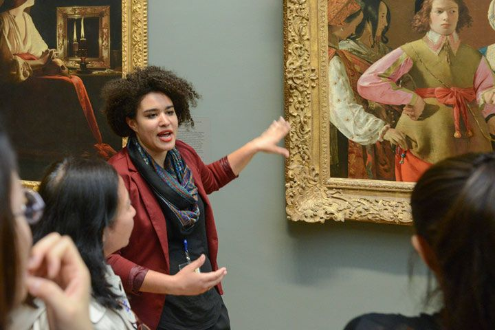Young woman talking in front of a painting
