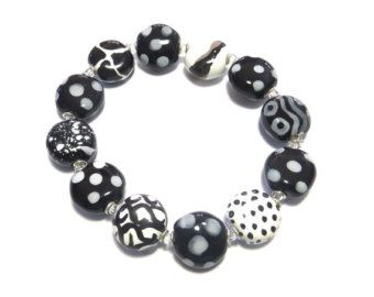 This beaded bangle is made with grey, black and white colored Kazuri beads, some of the beads have abstract designs or spots and dots and some are plain. The kazuri beads range in size from 1/4 of an inch to 3/4 of an inch in size. On this beaded bangle each bead is separated by three small metal spacer beads. It is a large size. The Kazuri beads are hand made and hand painted by women in Kenya. The Kazuri Bead business employes 360 women who are all paid fair wages and then the goo...