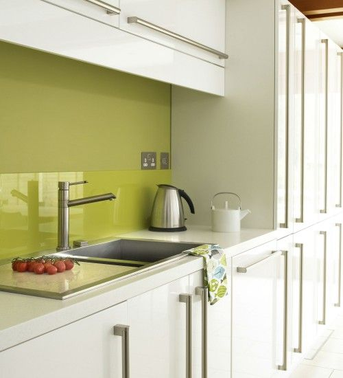 Cool and contemporary kitchen  Perk up a plain white kitchen with a bold splash of colour.  In a contemporary kitchen, swap a traditional tiled splashback for something more colourful.  Paint the wall in a contrasting colour, like this zesty lime, then fix a glass splashback to the wall to protect the paintwork.
