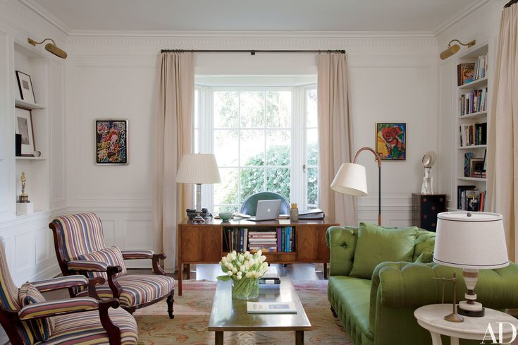 Paintings by Dubuffet (left) and Hans Hofmann flank a 1960s desk from J. F. Chen in the library of movie producer Steve Tisch's Beverly Hills, California, mansion, decorated by Peter Dunham. The circa-1870 armchairs are upholstered in a Robert Kime stripe, and the sofa is covered in a Claremont silk.
