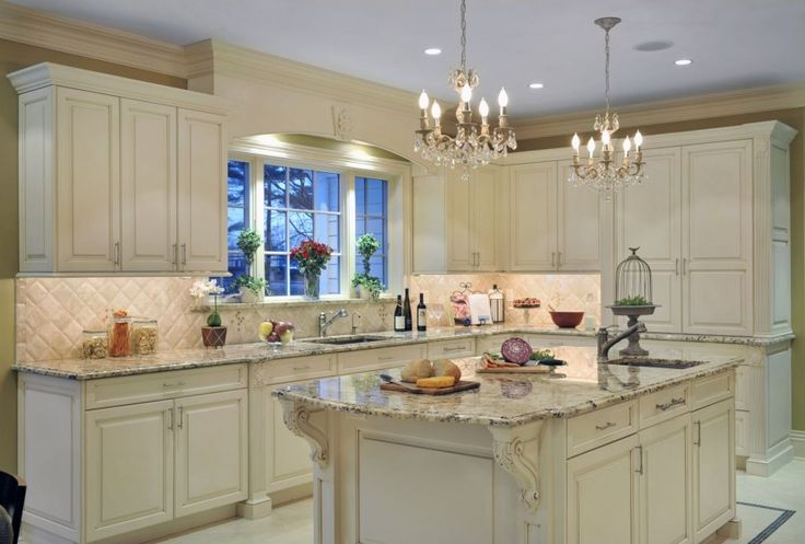 Light painted wood cabinetry fills this space, lit by traditional chandeliers, and topped by marble countertops.