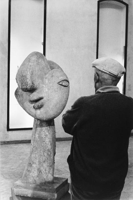 "Picasso standing in front of his sculpture ""Head of Woman with Hair Bun"", 1931, Photo by Antonio Cores."