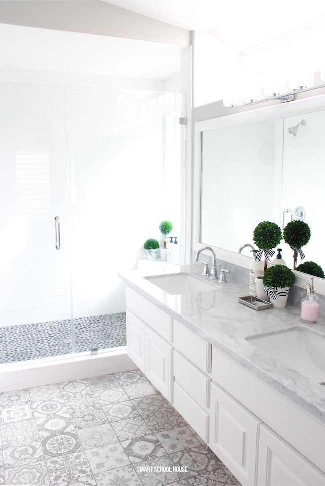 Gray and white bathroom ideas. Gray and white rustic patterned tiles. Rock shower floor. Glass shower doors. Marble countertops.