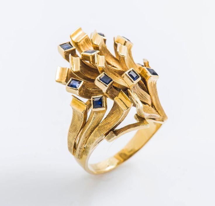 Bague gerbe moderniste en or jaune 18 carats (750 millièmes) brossé formant des lames, certaines serties d'un saphir carré. Taille de doigt : 49 Poids brut : 9,7 g  Adjugé: 900€