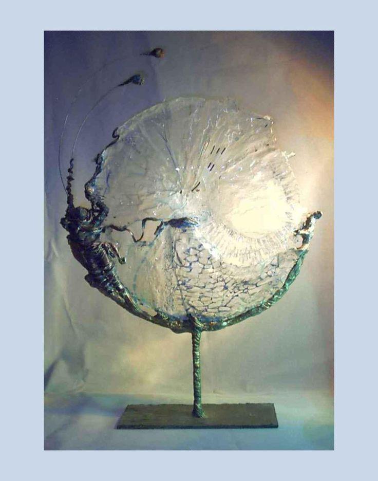 Scultura luminosa realizzata in terra refrattaria patinata ad effetto bronzo, metallo, resina e vetrofusione.  Dimensioni: larghezza cm. 42, altezza cm. 55, profondità  cm.20