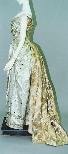 Бальное платье. Руфф, около 1888. Бледно-зеленый шелковый атлас, вышитый серебряными нитями и блестками, комплект из корсажа и юбки, трен из золотистой шелковой ткани-брокад с растительным орнаментом.