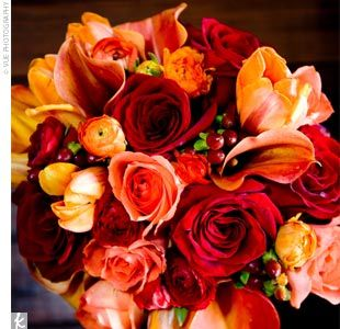 a bold bouquet of mango calla lilies and tulips, ranunculuses, roses, and hypericum berries in oranges and reds. The stems were wrapped in espresso brown ribbon.