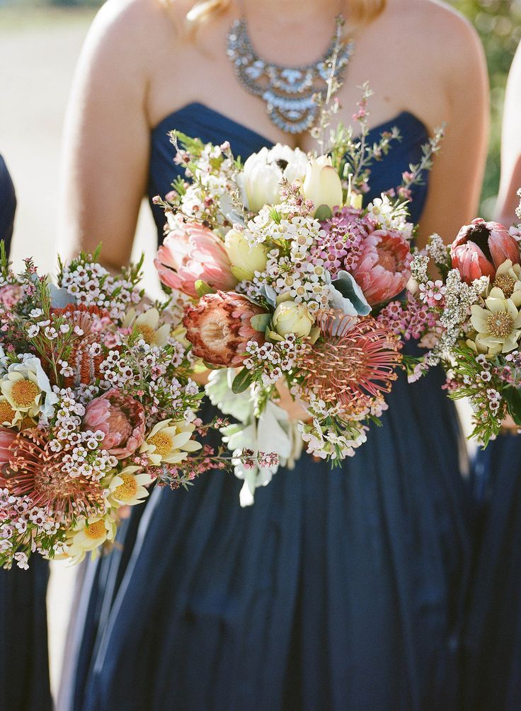Love the busy floral arrangement against the deep navy color of the bridesmaid's dresses. Featured Photographer: Yena, Sugarblush; Featured Florist: The French Petal