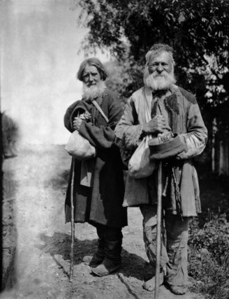 Two Russian Pilgrims holding hats and sticks, photo Netta Peacock. Russia, c.1902-10.