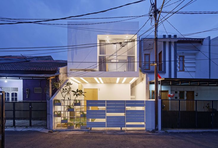 A staircase connecting a series of split levels ascends through a void at the centre of this house in Jakarta, which features a cantilevered upper storey.