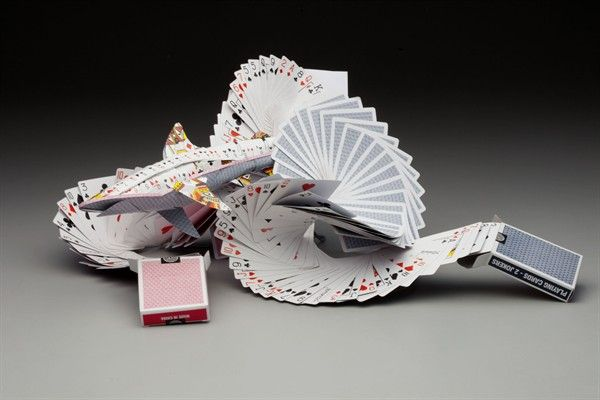 "Hannah Kim -- ""Card Shark"" Mixed media - playing cards and wire ""Influenced by the sculpture at the Fluor Daniel Engineering Building at Clemson University, I overlapped the playing cards to create a wave-like pattern and connected it with the repetition in the shark as well. I wanted to create a piece that translated the whimsicality of the pun, 'card shark,' by morphing the deck of cards into a sculptural shark coming out of waves of playing cards."" -- Coppell High School;"