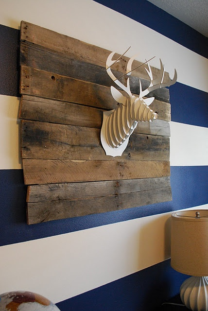 """cardboard deer head """"mounted"""" to upcycled wooden palette pieces."""