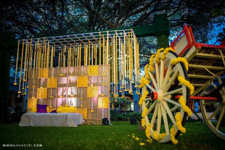 Yellow theme decor for a Mehendi setup! We love the way the cart wheel has been decorated!