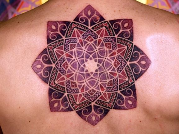 The pattern of curved lines appears almost animated, giving this flower mandala tattoo a lively appeal