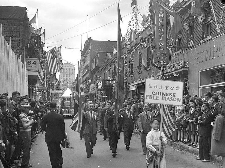 A Victoria Day parade on De la Gauchetière Street in the 1945 Montreal Chinatown with the Bell Telephone Building in the background.