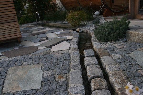 An der Stelle wo der Bachlauf den Gartenweg kreuzt, fliesst er zwischen einer Reihe Granit Großstein hindurch, um das Laufen zu erleichtern.