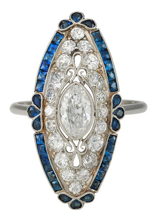 A SUPERB RING OF PLATINUM, WITH CALIBRE SAPPHIRE BORDER, TO PIERCED PLATINUM AND MARQUISE DIAMOND OF F/G COLOUR AND A TOTAL DIAMOND WEIGHT OF 1.55CTS.