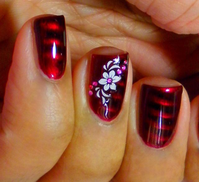 Red magnetic polish with a white flower stamped on it.