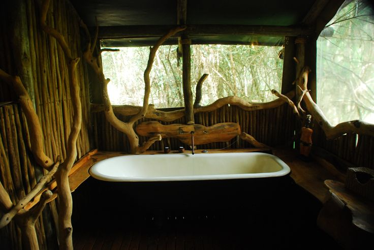 The bathrooms in the luxury tents are adorned with natural wood from the forests surrounding. Sibuya Game Reserve Forest Camp reached via boat along the Kariega River from Kenton on Sea, Eastern Cape, South Africa www.sibuya.co.za