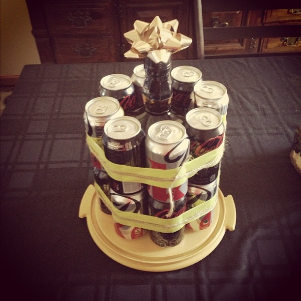 Jack and Coke cake // I made this for my boyfriend's birthday! He loves Jack Daniels, so there was no question about whether he would like it or not. I used a handle of Jack Daniels, 8 cans of Diet Coke, 8 cans of Coke Zero, green duct tape, twine, a gold bow, and the bottom of a cake container to carry it on.