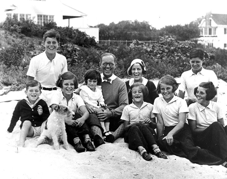 """The Kennedy Family at Hyannis Port, 04 September 1931. L-R: Robert Kennedy, John F. Kennedy, Eunice Kennedy, Jean Kennedy (on lap of) Joseph P. Kennedy Sr., Rose Fitzgerald Kennedy (behind) Patricia Kennedy, Kathleen Kennedy, Joseph P. Kennedy Jr. (behind) Rosemary Kennedy. Dog in foreground is """"Buddy"""". Photograph by Richard Sears in the John F. Kennedy Presidential Library and Museum, Boston."""