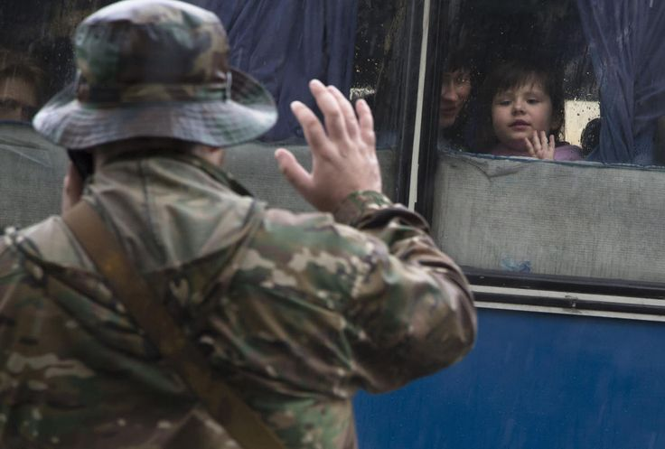 A Donetsk People's Republic fighter tells goodbye to his family departing as refugees to Russia in the city of Donetsk, eastern Ukraine Monday, July 14, 2014. Five busloads of Internally Displaced People from the towns of Slavyansk, Karlovka, Maryinka and Donetsk left here Monday morning for the Rostov region in Russia to ask for refugee status there.