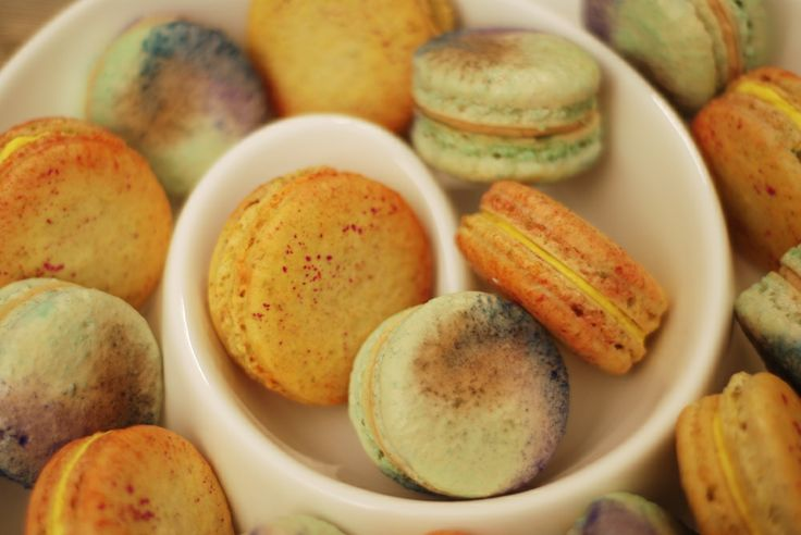 Handpainted Saffron-Orange Blossom macarons on Orange-Pistachio shells and Moroccan Spiced Coffee macarons.  Looks like a watercolour painting.