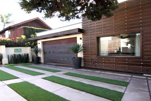 Horizontal wood slats facade,  Concrete and lawn front yard and driveway, toned wood garage door