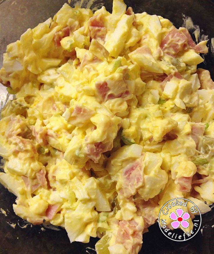 Eiersalade. 4 eieren, 4 plakjes schouderham, 1 bosuitje, 2 augurkjes zoetzuur, 1½ el halfvolle fritessaus, 1 tl mosterd, ½ el ketchup, 1 el Philadelpia naturel light, zout en peper.